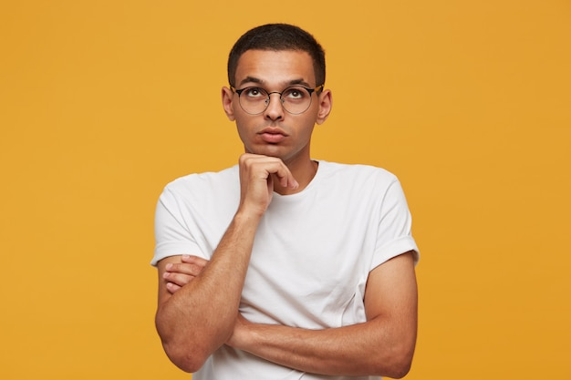 Portrait of attractive young man in glasses looks up ponders a thought or idea