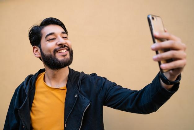 Ritratto di giovane attraente che cattura selfie con il suo telefono mophile contro il muro giallo.