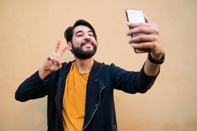 Portrait of attractive young man taking selfies with his mophile phone against yellow wall.