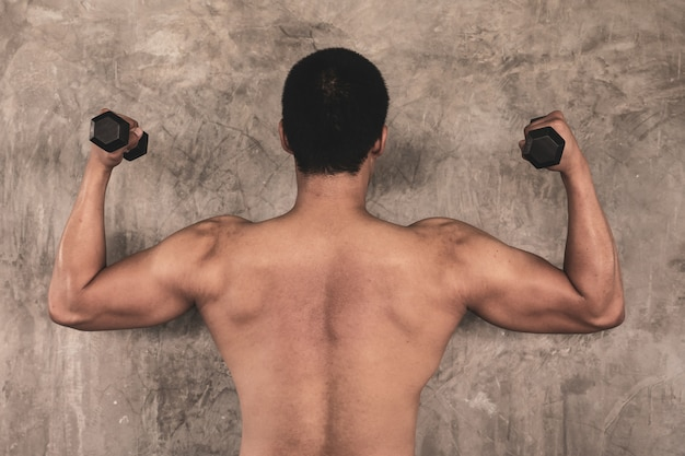 Portrait of attractive young man with dumbbell on grunge background.