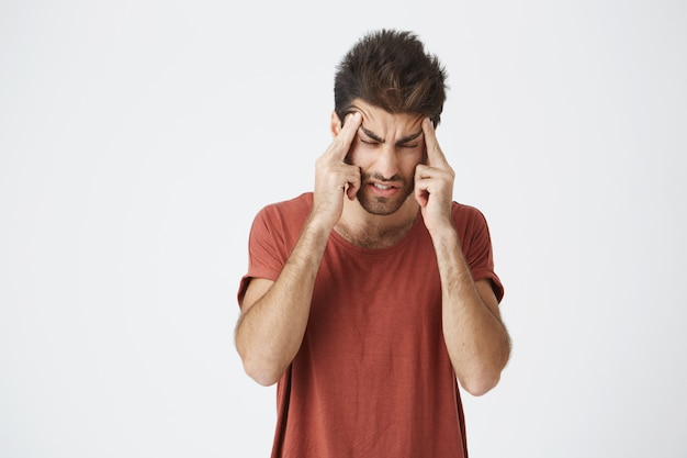 Portrait of attractive young spanish male wearing red t-shirt with stressful and frowny face, squeezing head with hands having headache after sleeping only for few hours.