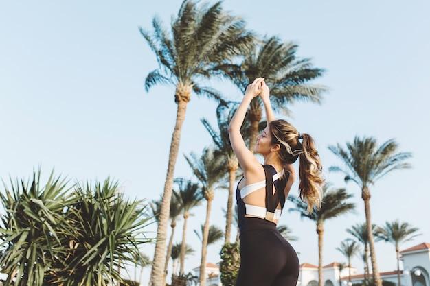 ヤシの木、青い空にストレッチ魅力的な若いスポーツウーマンの肖像画。晴れた朝、トレーニング、モチベーション、フィットネス、トレーニング、リラクゼーション。