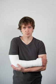 Portrait of attractive young upset caucasian man with plaster cast on his hand on a white wall background.