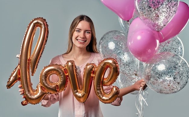 Portrait of attractive young woman in blouse is standing on grey with air balloon labeled love in hands and heart shaped balloons.
