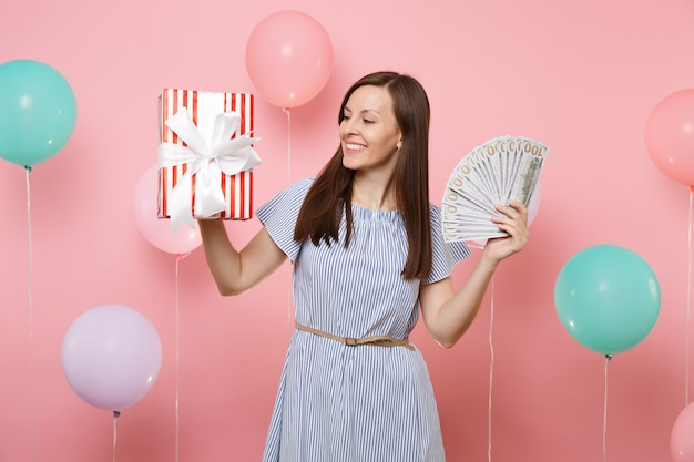 Portrait of attractive young woman in blue dress holding bundle lots of dollars cash money looking on red box with gift present on pink background with colorful air balloons. birthday holiday party.