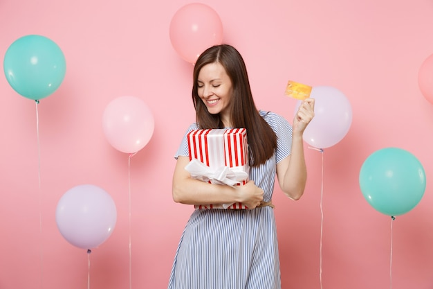 Portrait of attractive young woman in blue dress holding credit card and red box with gift present on pastel pink background with colorful air balloon. birthday holiday party, people sincere emotions.