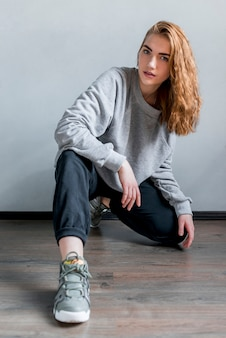 Portrait of an attractive young woman crouching on hardwood floor