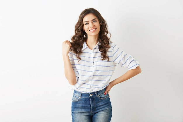Portrait of attractive young woman dressed in casual fashion summer style, shirt and jeans, curly hair, smiling, looking in camera, beautiful model isolated, white teeth, pretty face, relaxed pose