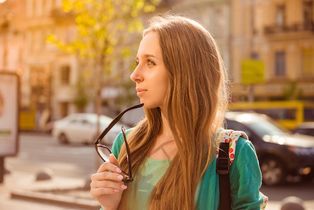 Portrait of attractive young woman having walk in city