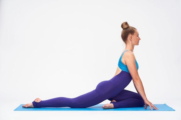 Портрет привлекательная молодая женщина в спортивном костюме, делающая упражнения на растяжку на циновке