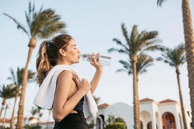 手のひらと空のボトルからスポーツウェア飲料水で肖像画の魅力的な若い女性。熱帯都市、晴れた朝、目を閉じてリラックス、ワークアウト。