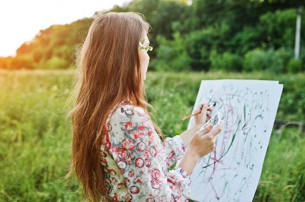 Portrait of an attractive young woman in long dress painting with watercolor in nature.