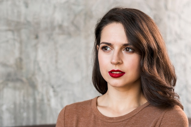 Portrait of an attractive young woman looking away against concrete wall