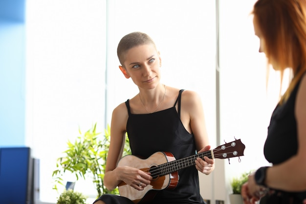 Portrait of attractive young woman playing on brown ukulele and spending time with friend. short haired lady wearing black dress. big light room. artist and music concept