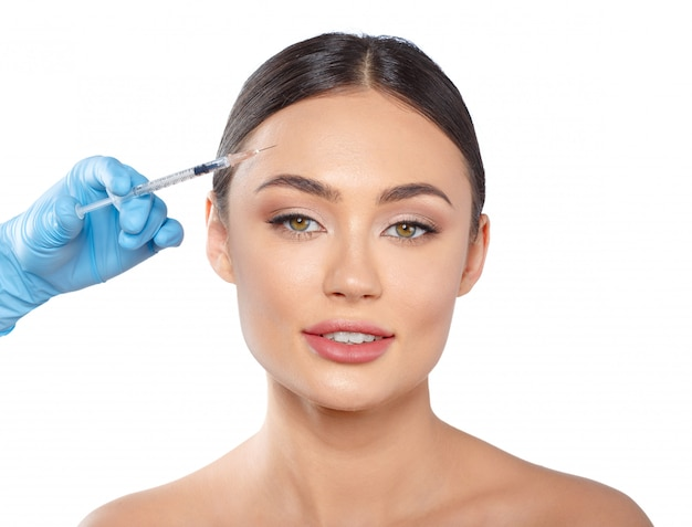 Portrait of an attractive young woman receiving botox treatment.