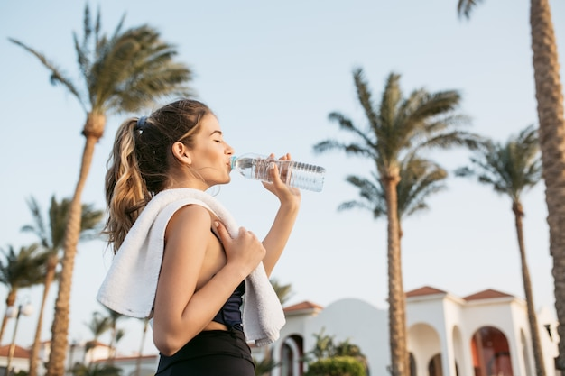 Portrait attractive young woman in sportswear drinking water from bottle on palms and sky. tropical city, sunny morning, relaxing with closed eyes, workout.