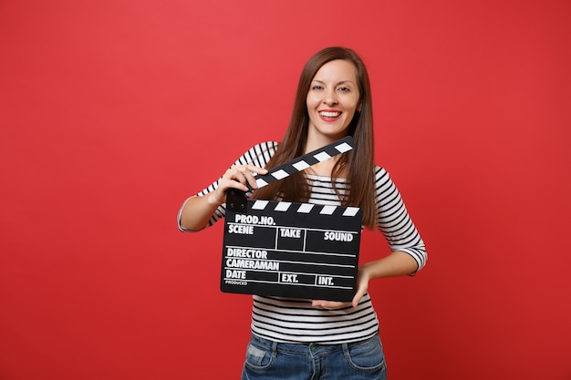 Portrait of attractive young woman in striped clothes holding classic black film making clapperboard isolated on bright red background. people sincere emotions, lifestyle concept. mock up copy space.