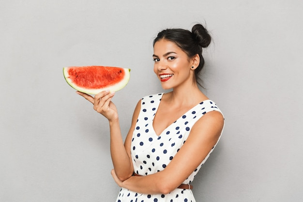 Portrait of an attractive young woman in summer dress isolated, holding watermelon slice