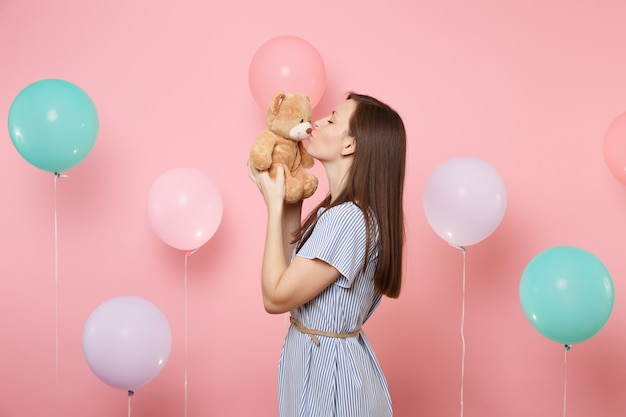 Portrait of attractive young woman wearing blue dress holding and kissing teddy bear plush toy on pink background with colorful air balloons. birthday holiday party, people sincere emotions concept.