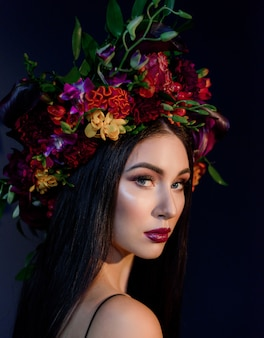 Portrait of attractive young woman with bright make-up dressed in big colorful floral wreath