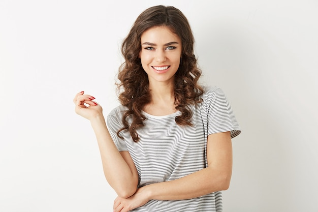 Portrait of attractive young woman with curly hair smiling isolated on white studio background, dressed in t-shirt,