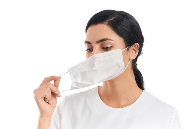 Portrait of attractive young woman with dark hair getting off medical protective mask on white
