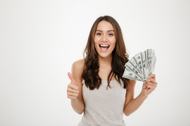 Portrait of attractive young woman with long hair holding lots of money cash, smiling on camera showing thumb up over white wall