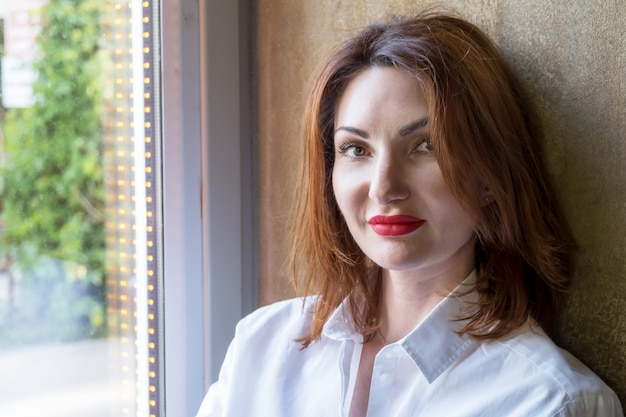 Portrait of an attractive young woman with red hair in white shirt on the windowsill by the large window in a cafe. woman looks into camera