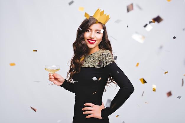 Ritratto attraente giovane donna con corona gialla che celebra la festa di compleanno su uno spazio bianco.
