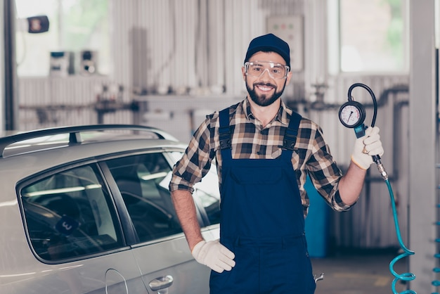 Portrait of auto mechanic in blue overall checkered shirt protective spectacles cap