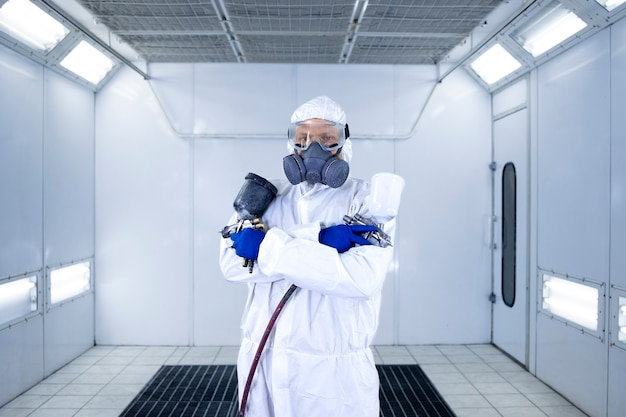 Portrait of automobile painter standing in paint chamber workshop holding painting gun.