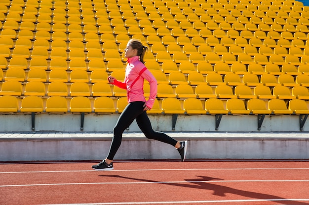 Portrait of ayoung woman running at the stadium outdoors