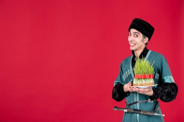 Ritratto dell'uomo azero in costume tradizionale che dà semeni sulla festa etnica del ballerino rosso novruz primavera