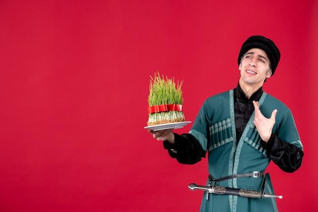 Ritratto dell'uomo azero in costume tradizionale che dà semeni sulla primavera di festa etnica del ballerino rosso