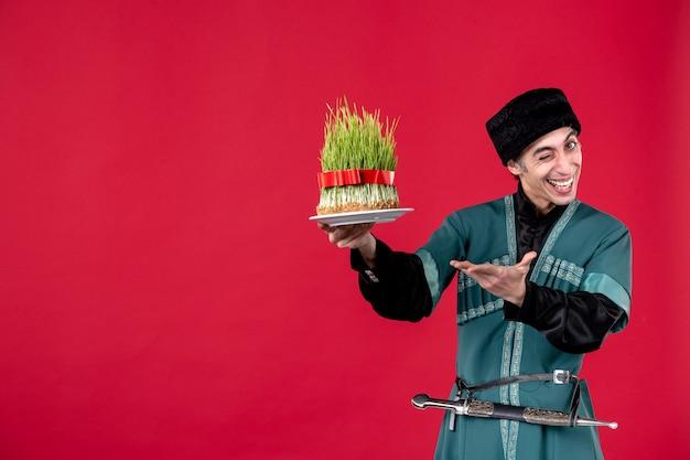 Ritratto dell'uomo azero in costume tradizionale che dà semeni sulla festa etnica del novruz del ballerino rosso