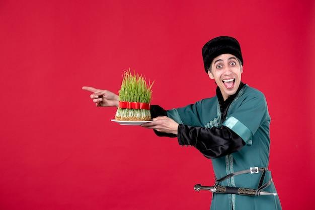 Ritratto dell'uomo azero in costume tradizionale che dà semeni sulla festa del ballerino di primavera etnica rossa novruz