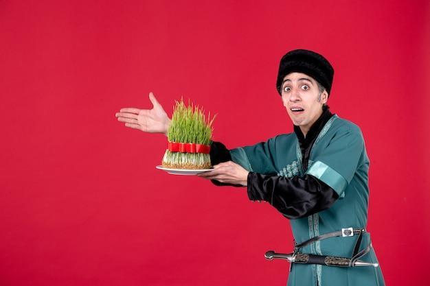 Ritratto dell'uomo azero in costume tradizionale che dà semeni sul ballerino di primavera etnico rosso novruz