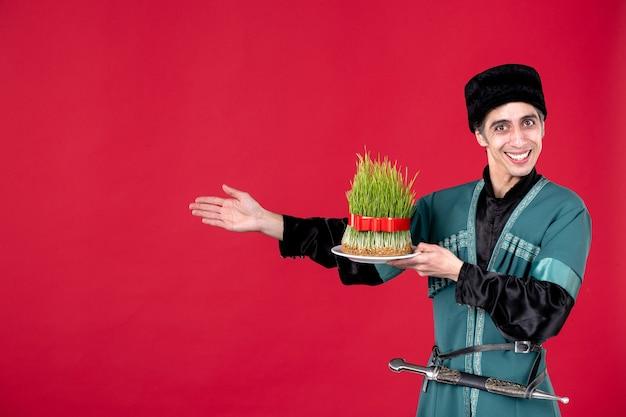 Ritratto di uomo azero in costume tradizionale che dà semeni durante la festa del ballerino di primavera rossa novruz