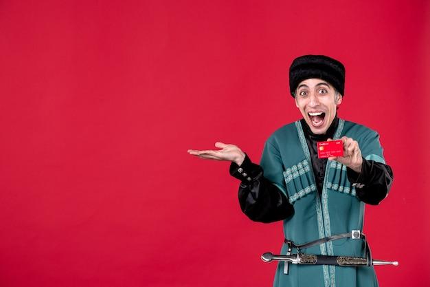 Ritratto dell'uomo azero in costume tradizionale che tiene la carta di credito sul colore rosso del novruz etnico della molla dei soldi