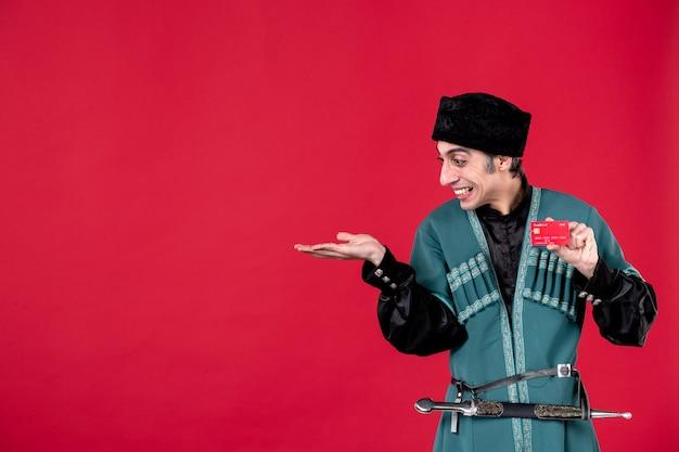 Ritratto di uomo azero in costume tradizionale in possesso di carta di credito su denaro rosso primavera etnica colori novruz