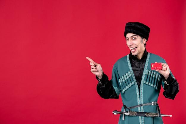 Ritratto di uomo azero in costume tradizionale in possesso di carta di credito su denaro rosso primavera