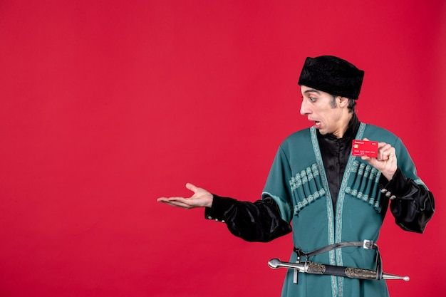 Ritratto dell'uomo azero in costume tradizionale che tiene la carta di credito sul colore rosso del novruz etnico dei soldi della molla
