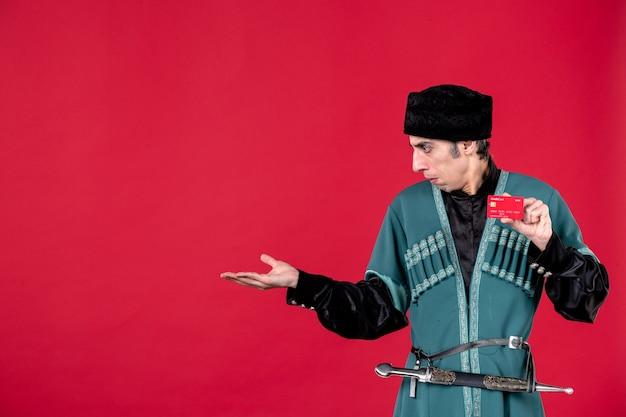 Ritratto di un uomo azero in costume tradizionale che tiene in mano una carta di credito su una foto di novruz etnica con soldi primaverili rossi
