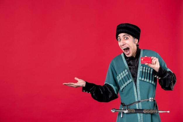 Ritratto di uomo azero in costume tradizionale in possesso di carta di credito su red spring money novruz