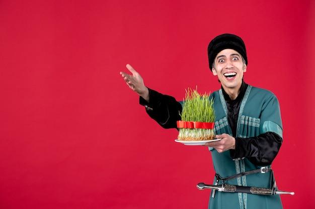 Ritratto di uomo azero in costume tradizionale che tiene seme verde su rosso