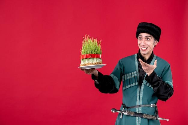 Ritratto di uomo azero in costume tradizionale che tiene semeni su ballerino rosso novruz primavera etnica