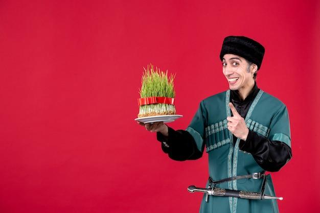 Ritratto di uomo azero in costume tradizionale che tiene semeni su ballerino rosso vacanza novruz primavera etnica