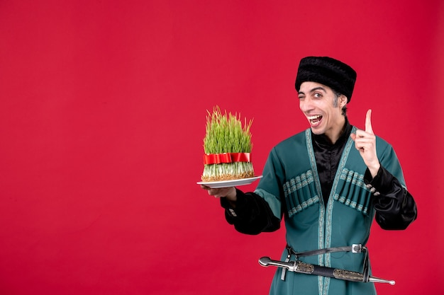 Ritratto di uomo azero in costume tradizionale che tiene semeni su ballerino rosso festa primavera etnica