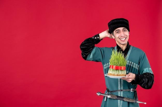 Ritratto di uomo azero in costume tradizionale che tiene semeni su ballerino etnico primavera novruz rosso