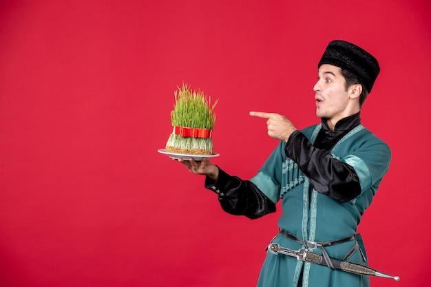 Ritratto di uomo azero in costume tradizionale azienda semeni studio shot concetto rosso ballerino novruz primavera